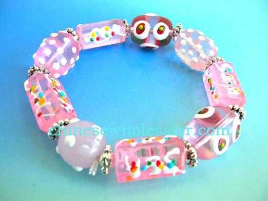Handmade China import bracelet supplied for reatil sale. Fashion stretchy pink bracelet with multi red white hand-painted Chinese lampwork glass bead and flat silver beads design