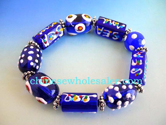 Wearable art jewelry distributed online from China manufacturer. stretchy blue bracelet with multi red white hand-painted Chinese lampwork glass bead and flat silver beads design