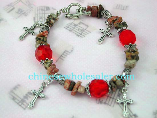 Silver charm bracelet supplied by China wholesale distributor. Silver charm bracelet with rock styled beads, red gemstone beads, and silver cross charms dangling with toggle clasp for closure.t