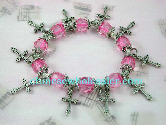 Gemstone charm bracelet supplied at wholesale price from China international importer. Pink color beads with silver cross charms and flowery beads on strecthy charm bracelet