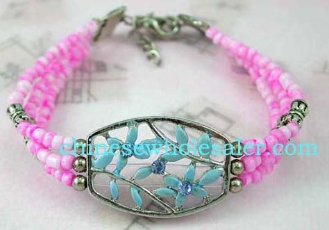 Gemstone jewelry sold online from china manufacturing wholesaler. Fashion bracelet with hollow oval shape holding blue flower design inlaid with blue gemstones. Three pink beaded string around wrist with silver beads added for decor.