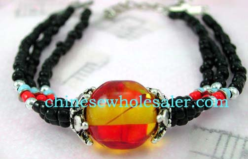 Unique beaded jewelry supplied by international wholesaler. Bracelet with three small black beaded strings each holding a silver, red, and blue bead that come together with orange and yellow glass bead in center between two silver decorated stones..