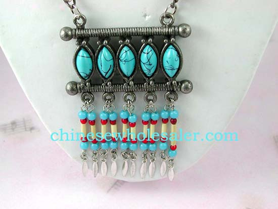 Wholesale jewelry and fashion gift manufacturer distributes Tibetan style dangling necklace with turquoise cats eye shaped beads above columns of red, white, and blue beads with feather design hanging below..