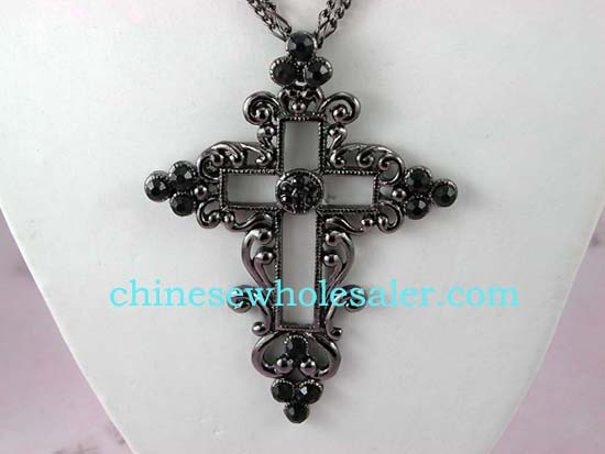 Cross necklace wholesale jewelry supplier distributes Fancy cut-out cross necklace with floral design around edges and purple cz stones inlaid, hanging on double string chain..
