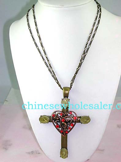 Direct jewelry fashions from China wholesale distributor. Cross pendant with yellow oval shaped stones at each tip and copper colored heart inlaid with vine design and red cz gems..