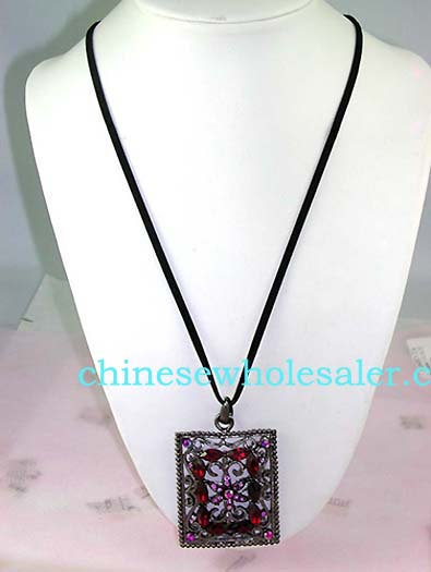 Wholesale crystal fashion import distributors supply Picture frame shape pendant with purple cz flower design at center surrounded by red cz stones atop vine decor and has four purple cz gems in each corner..