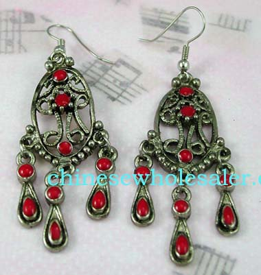 China earring supplier distributes wholesale jewelry. Gypsy style fish hook, oval cut-out earrings with intricate design and three red stones in center, three rows of pearl shaped danglers inlaid with red stones hang below.