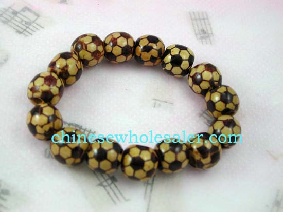 Buying agents distristributes China jewelry fashion products. Dark brown soccer ball design on yellow wooden bead bracelet
