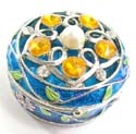 Round enamel jewelry box motif filigree flower holding 5 orange shiny beads and a pearl bead inlaid on lid with pinky flower decor around, enamel in blue color