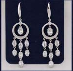 Wholesale earring fashions supplied by online import jewelry company. Star burst made of cz stones hang in the center and below rhodium plated hoop.
