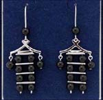 Faux pearl jewelry wholesaler imports manufactured fashion earring from China. Figure design created from imitation black pearls hanging from rhodium plated arms