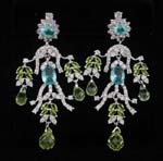 Jewelry gift wholesaler imports and exports fashion supplies. Ornate earings with flowery shrub design, transluscent blue and green cz chrystals hanging from rhodium plated branches inlaid with clear cz stones.